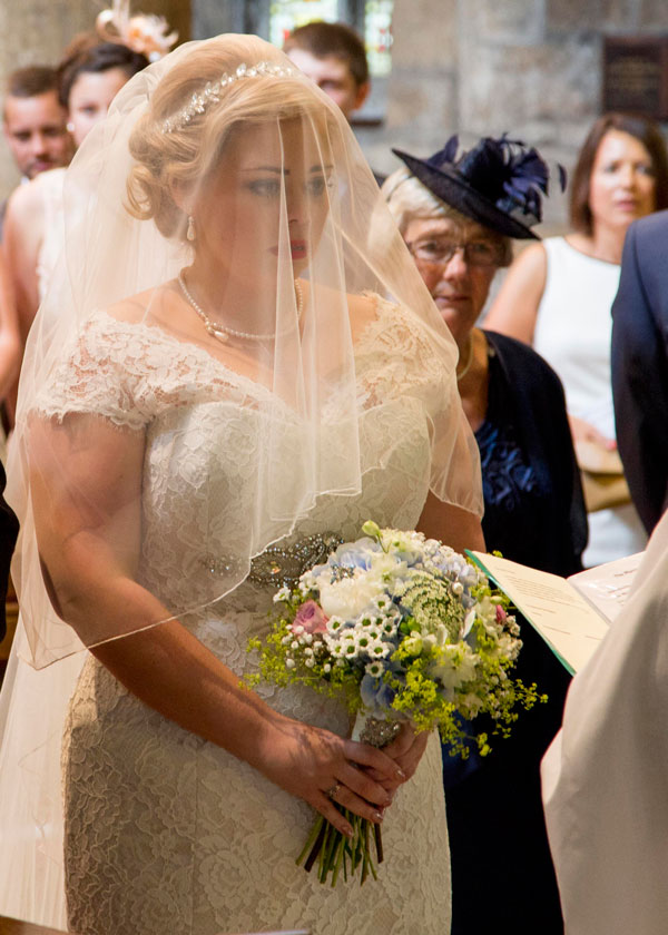 Bride walking down the aisle with veil covering her face