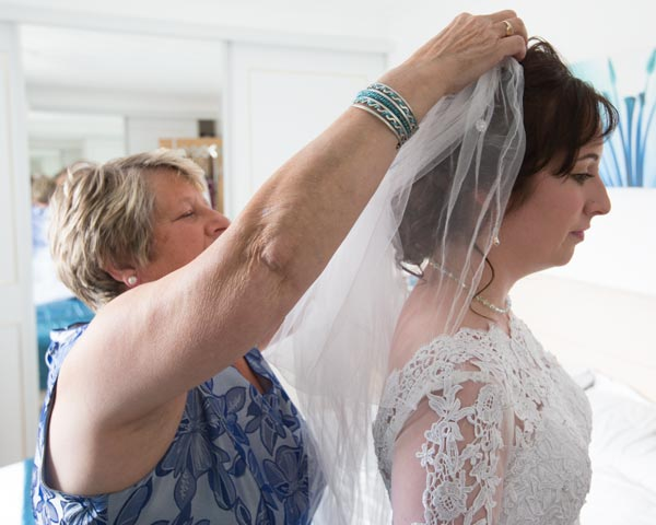 Mother of the bride putting white veil into brides hair