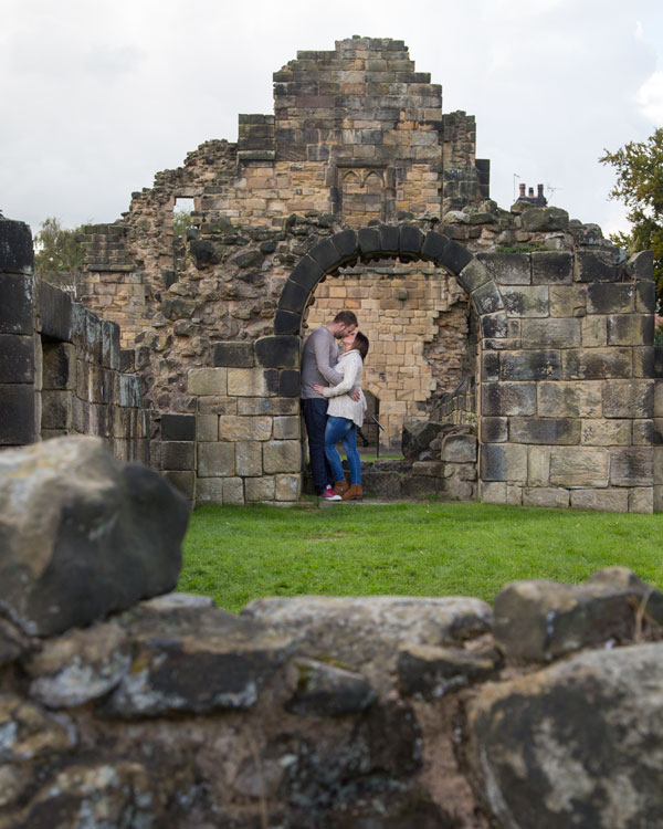 A couple on a pre-wedding shoot at Monk Bretton Priory Barnsley kissing in the ruins