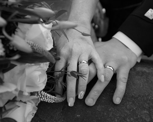 Bride and Grooms hands on stone wall next to bouquet showing wedding rings