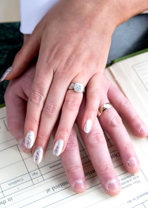 Bride and Grooms hands on register with non matching wedding bands and Bride also wearing engagement ring first
