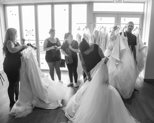 Black and white photograph of people organising wedding dresses in preparation for the Marie Blanche Bridal catwalk