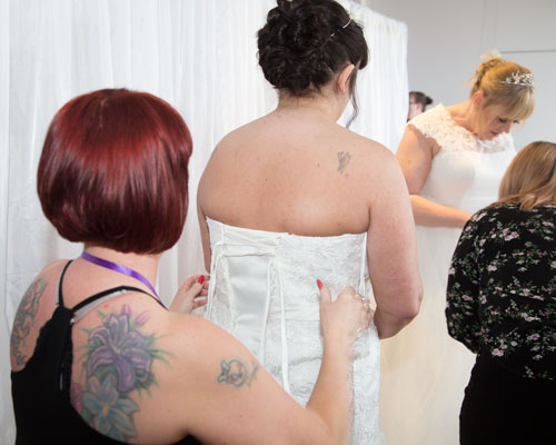 Wedding dress being fastened on one of the models at the Marie Blanche Bridal catwalk show