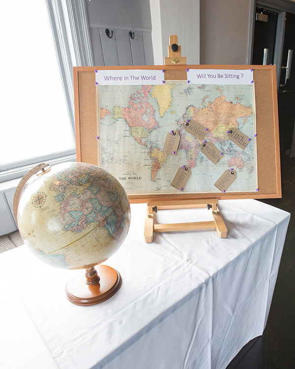 Globe and world map table plan at travel themed wedding