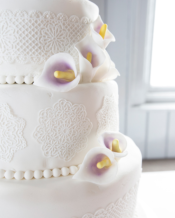 Close up of the wedding cake with purple lillies and white iced lace