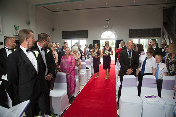 Bridesmaids walking down red carpet aisle in purple dresses with matching bouquets