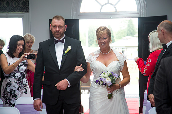 Bride and Son walking down the aisle together at Old Weighing room Doncaster Racecourse