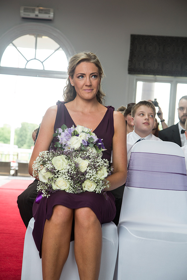 Bridesmaid in purple dress holding the bouquets during the wedding ceremony at The Old Weighing Room Doncatser racecourse