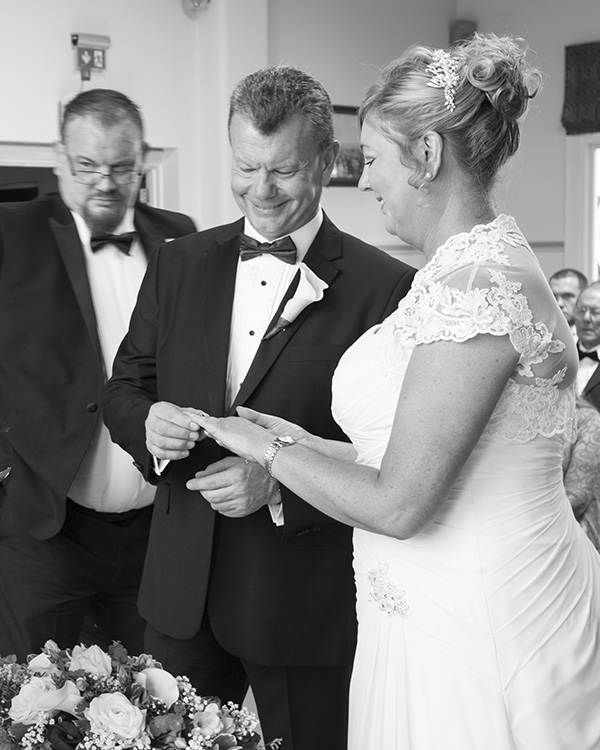 Bride and groom exchange rings black and white