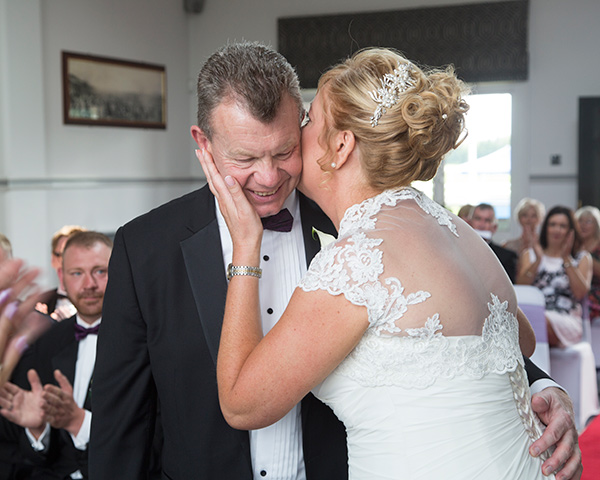 Bride kisses groom on the cheek during their wedding ceremony at the Old Weighing Room Doncaster racecourse
