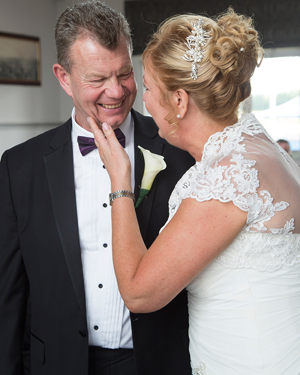 Bride and Groom looking at each other and laughing during their wedding ceremony Doncaster Racecourse Old Weighing room