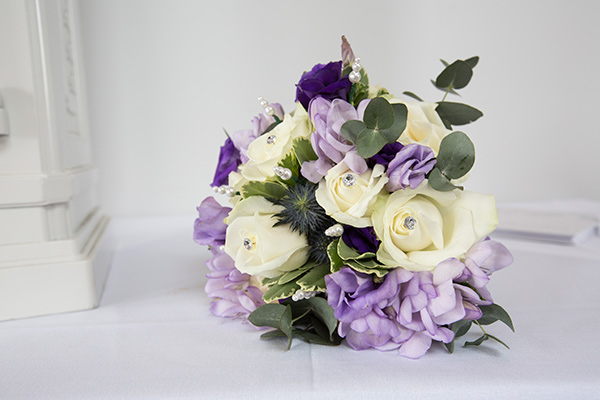 Purple and white wedding bouquet on white clothed table against a white wall