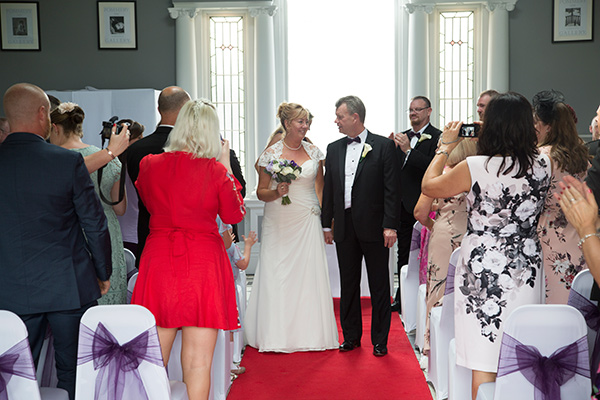 Bride and Groom facing guests at the end of the wedding ceremony while standing on the red carpet