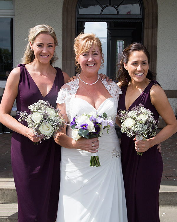 Bride with her two adult bridesmaids in their purple dresses all holding matching bouquets