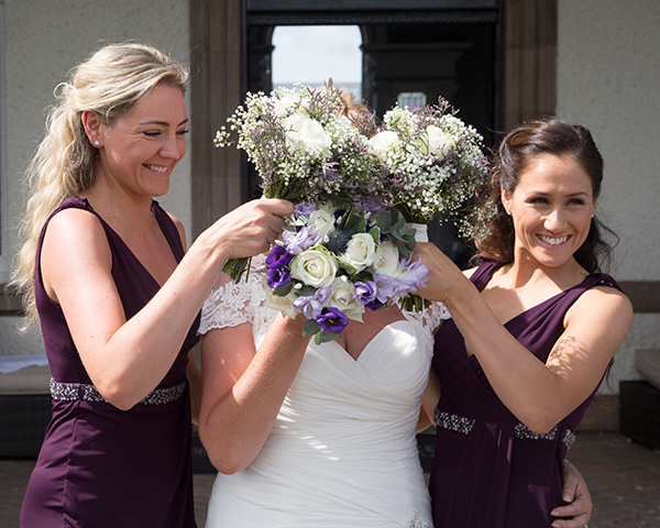 Bridesmaids covering brides face with bouquets outside the Old Weighing Room at Doncaster Racecourse
