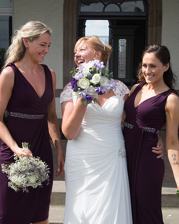 Bridesmaids and Bride laughing with bouquets outside the old weighing room at doncaster racecourse
