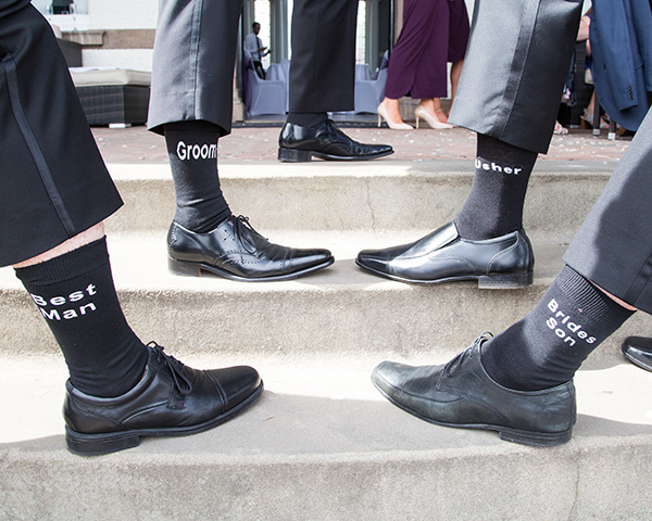 Groom and Groomsmen showing off their personalised black socks on the steps of the old weighing room doncaster racecourse