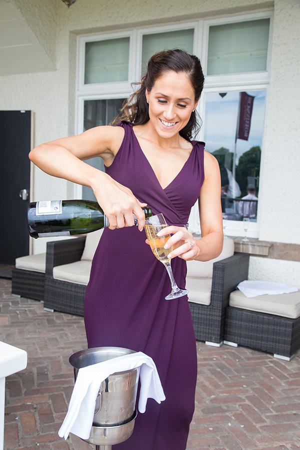 Bridesmaid pouring a glass of champagne outside the old weighing room at Doncaser Racecourse and smiling