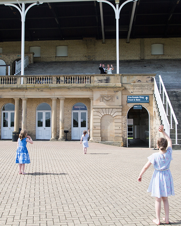 Three girls waving at the bride and groom from the ground as they stand in the stadium at Doncatser racecourse