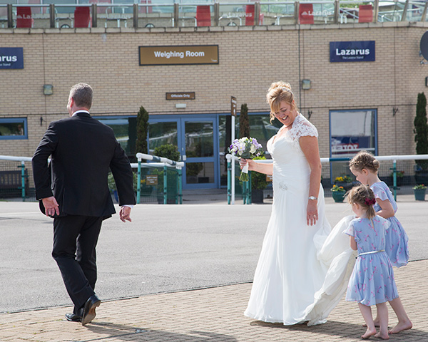 Children in blue dresses helping the bride carry her train across the car park at Doncaster Racecourse wedding