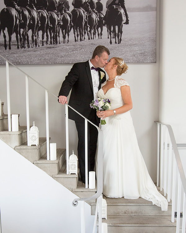 Bride and Groom kissing on the steps inside the old weighing room at Doncaster Racecourse on their wedign day
