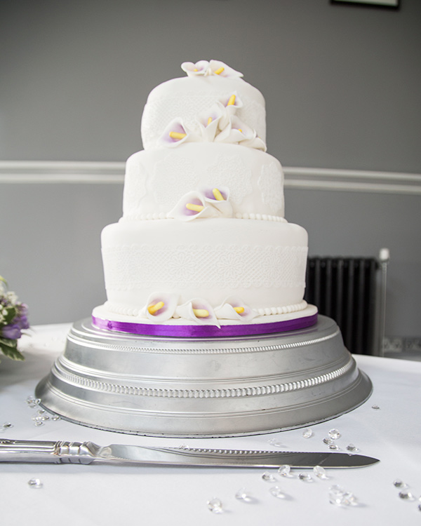 Purple and white wedding cake with purple lillies and purple ribbon and white iced lace