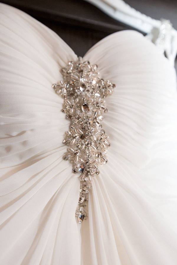Wedding dress hanging on brown wardrobe showing diamond embelishment