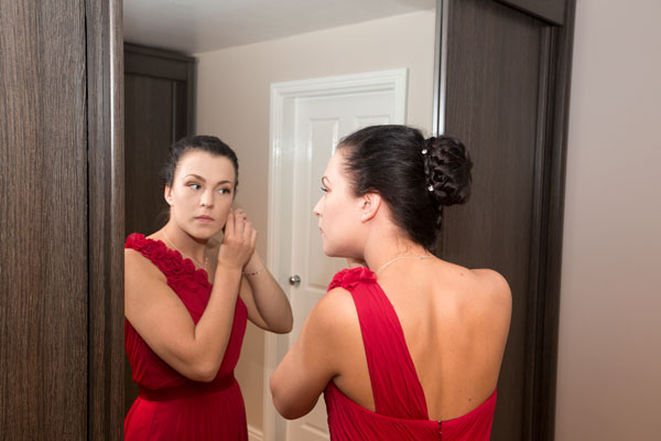 Bridesmaid standing in front of mirror putting in earrings