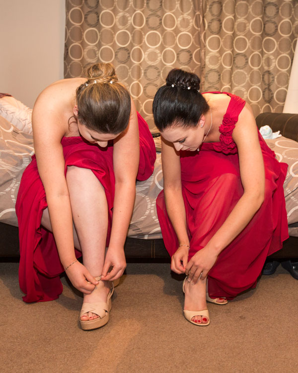 Two bridesmaids in red dresses sitting on a bed fastening their shoes