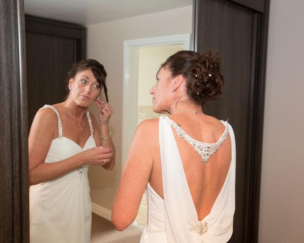 Bride in front of mirror putting in earrings