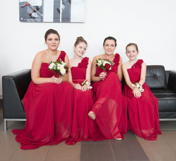 Bridesmaids in red dresses waiting at New York Stadium rotherham for bride to arrive