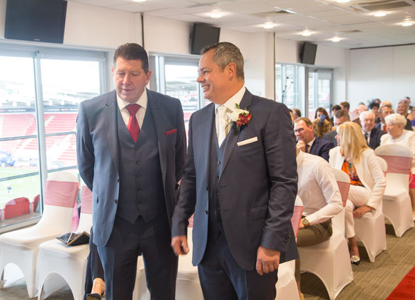 Groom and best man standing at the front of the New York suite wedding venue Aesseal stadium Rotherham