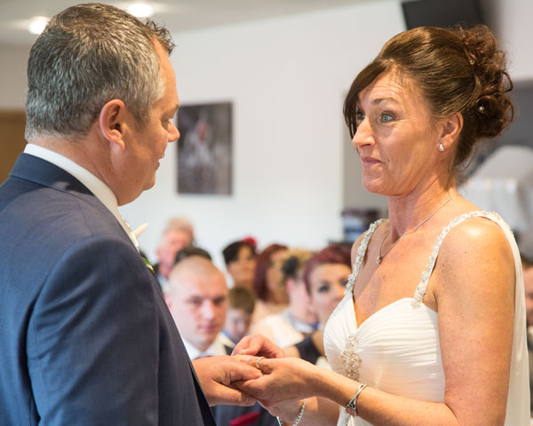 Bride giving ring to Groom during the wedding ceremony New York Stadium Rotherham