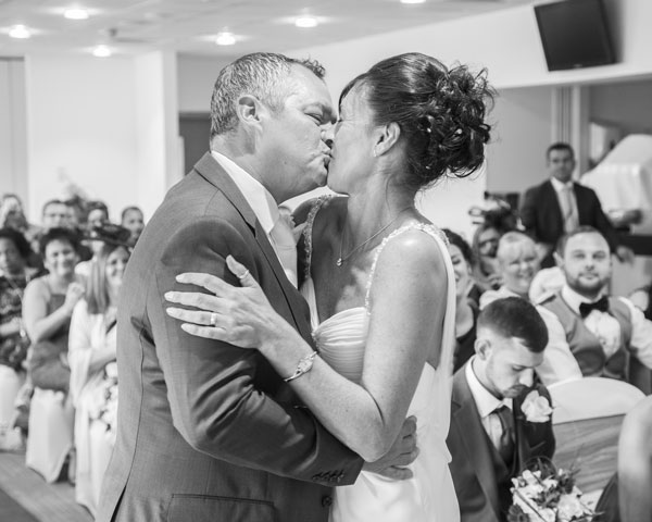 Bride and groom first kiss as husband and wife black and white