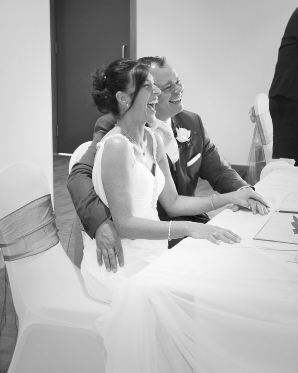 Bride and Groom laughing while signing register New York Suite Rotherham