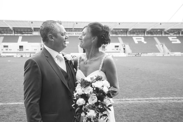 Black and white Bride and Groom looking at each other at the side of the pitch New York Stadium Rotherham