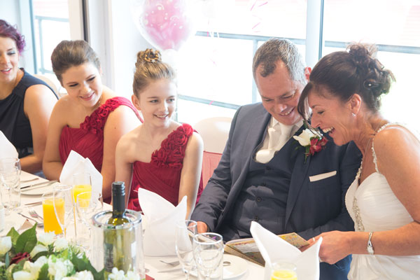 Top table looking at gifts and laughing together Aesseal stadium wedding Rotherham