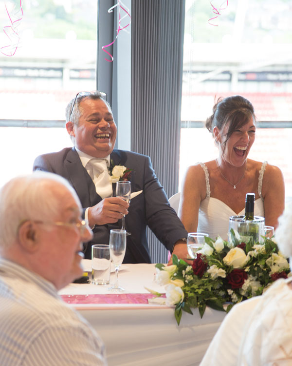 Bride and Groom Luaghing at the top table New York Stadium Rotherham