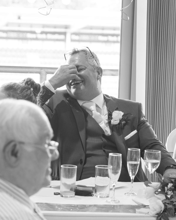 Groom laughing with embarrassment during speeches