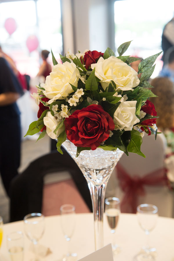 Red white and green flower centerpieces in giant martini glass at New York Stadium Rotherham
