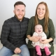 Couple holding their baby daughter on their kneww and smiling barnsley photography