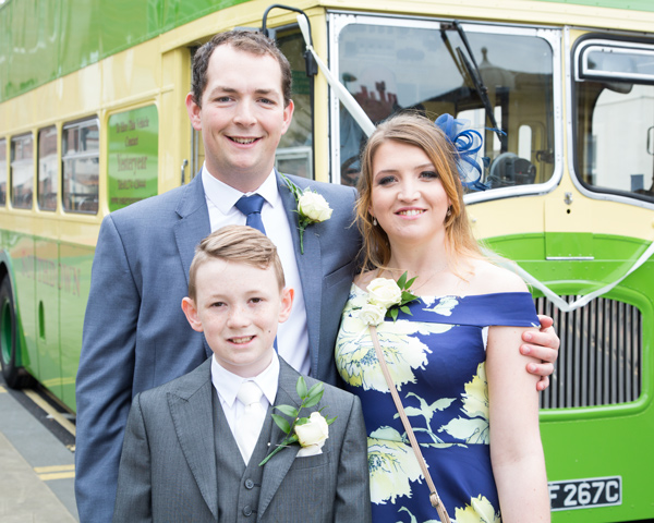 Family of three standing in front of a green double Decker bus