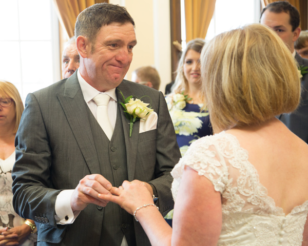 Bride and groom exchanging rings in side Barnsley Town Hall