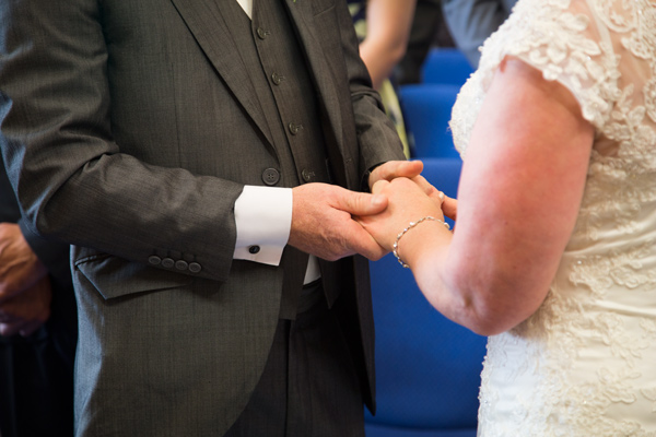 Bride and Groom holding hands during the exchange of the rings at Barnsley Town Hall wedding