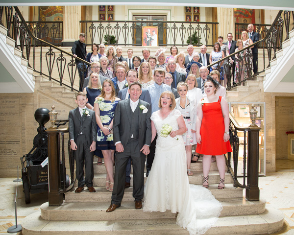 Bride and Groom with all their guests pulling silly faces on the staircase inside Barnsley town hall