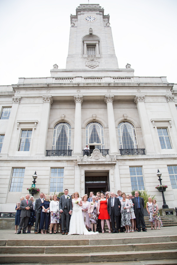 Full wedding party outside Barnsley town hall with the clock showing