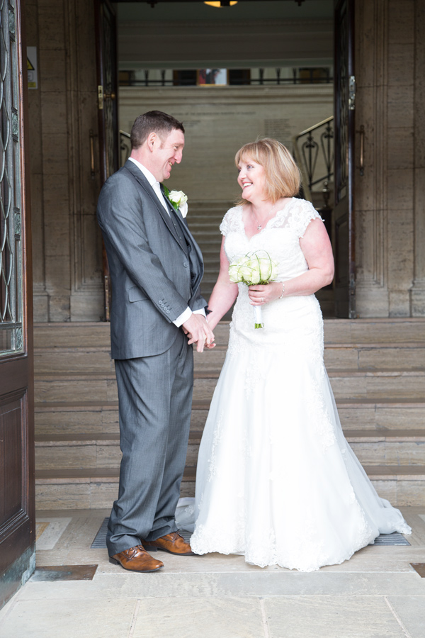 Bride and Groom laughing together in the entrance to Barnsley Town Hall