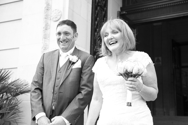 Bride and Groom laughing while walking out of Barnlsey Town Hall on their wedding day