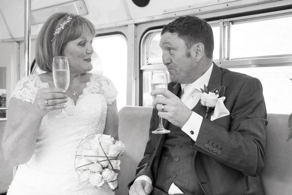 Bride and Groom holding champagne on the seat of their wedding bus