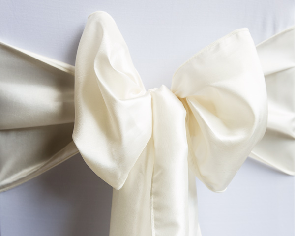 Cream satin bow on the back of a white chair by Wickham & taylor room styling